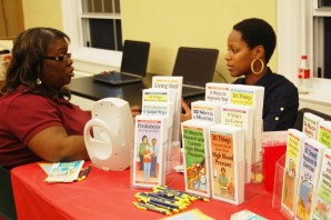 Yvette Bailey sits at a table at the Health Fair and offers pamphlets and tips. The first 85 students that attended the fair received a free five-year health screening. (Brittany Moore/Guilfordian)