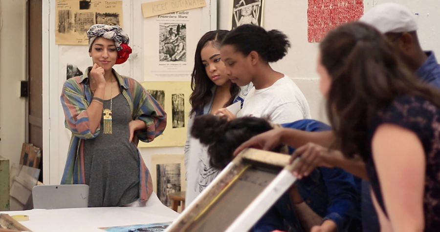 Saba Taj creates political posters along with students during an event open to the public on Wednesday, April 5 at the Hege-Cox Printmaking Studio in Greensboro, North Carolina. // Photo courtesy of Erin Kye