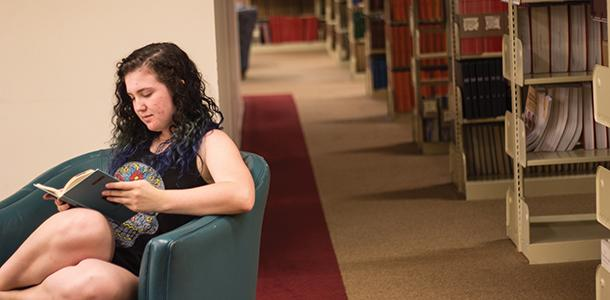 First-year Katie Ssan Filippo reads in the lower level of the library. Library staff recently re-shelved lesser-used books in a storage space in the basement, freeing up room for new technologies on the second floor.