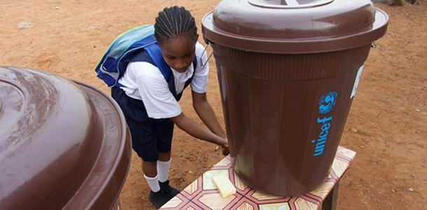 A+girl+cleans+her+hands+in+Monrovia%2C+Liberia.+