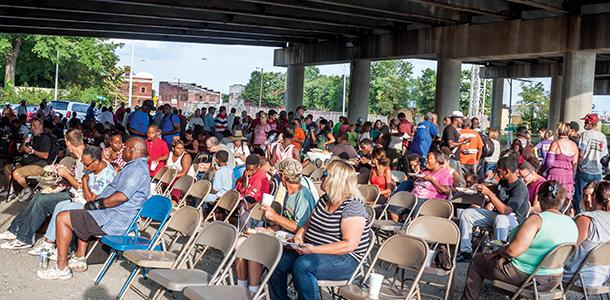 Worshipers sit at Church Under the Bridge, an open-air church service and meal for people experiencing homelessness downtown.