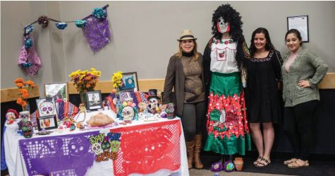 Latino Family Center staff Maria Harkins, Kelly Morales and Alejandra Vazquez stand beside an altar from Dia de los Muertos during the exhibition hosted by Caza Azul on Sat. Nov. 5.