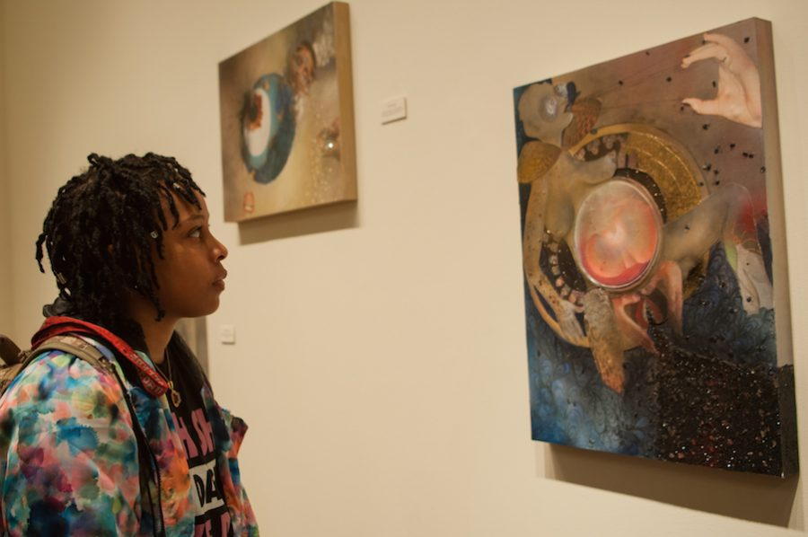 Guilford College student Essence Abraham 19 looks at the work of Saba Taj in new ways after attending a panel discussion with the artist on Tuesday, April 4, 2017 in the main gallery of Hege Library at Guilford College in Greensboro, North Carolina. Photo by Francesca Benedetto/Guilfordian