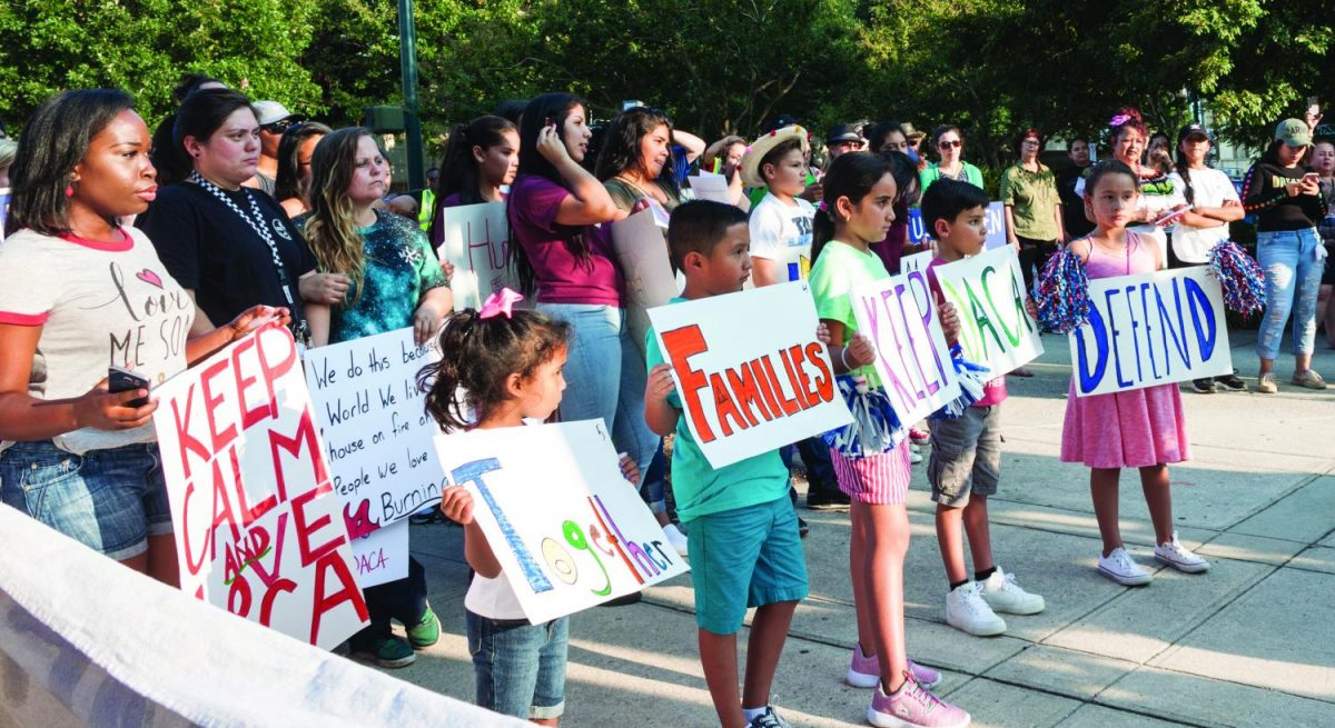Young children hold handmade posters to protest Donald Trump's announcement to repeal DACA while older demonstrators stand behind them in solidarity at the peaceful march towards LeBauer Park in Greensboro on Monday, Sept. 5, 2017.// Photo by Fernando Jimenez/The Guilfordian