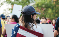 Chrisitina Gallegos, first-year student at Elon university, marched through downtown Greensboro wrapped in the United States flag to stand in solidarity with DACA receipients.// Photo by Fernando Jimenez/The Guilfordian
