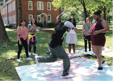 Assistant Professor of Art Antoine Williams and MiKayla Jones '19 dance at the Art on the Quad event on Wednesday afternoon, Sept. 20, 2017. Williams and Jones have shoe covers on their feet to decorate the large canvas with chalk as they dance. // Photo by Abigail Bekele/The Guilfordian
