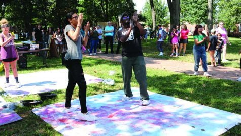 "Andrea Muniz '21, left, and Antoine Williams, assistant professor of art, dance at Art on the Quad on Wednesday, Sept. 20. 2017. Muniz and Williams have bags on their feet that decorate a large canvas with chalk as they dance, an activity known as ""Dance and Draw.""/Photo by Abigail Bekele/ The Guilfordian"