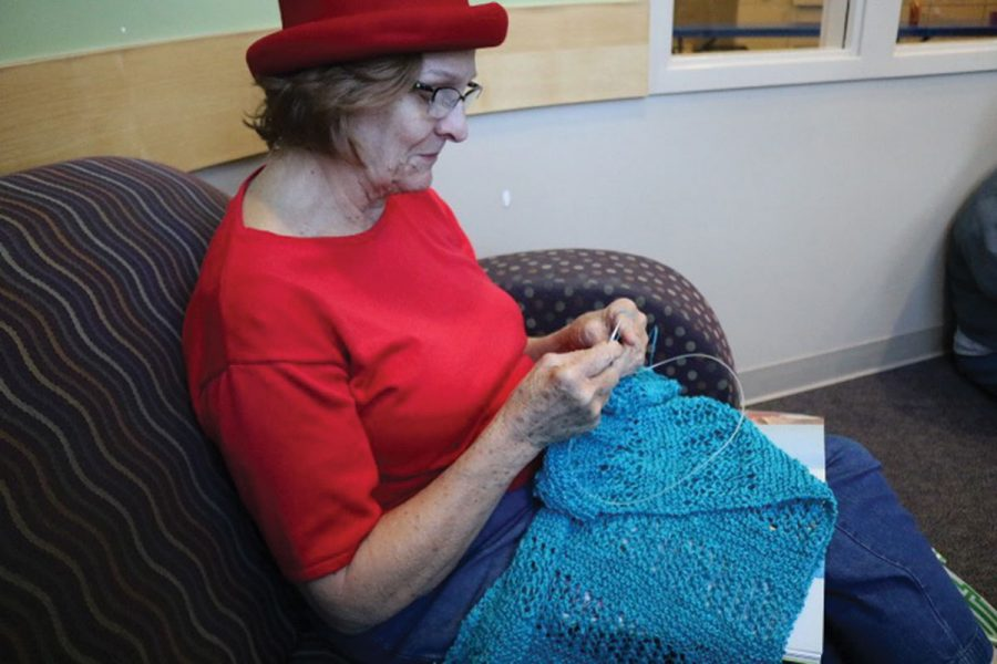 While waiting for students to arrive at her knitting class, Carol Phillips, a resident of Jamestown and knitter for 50 years, works on her latest creation, a lace blue shawl, at the Hemphill Branch Library. Photo by Praveena Somasundaram/The Guilfordian