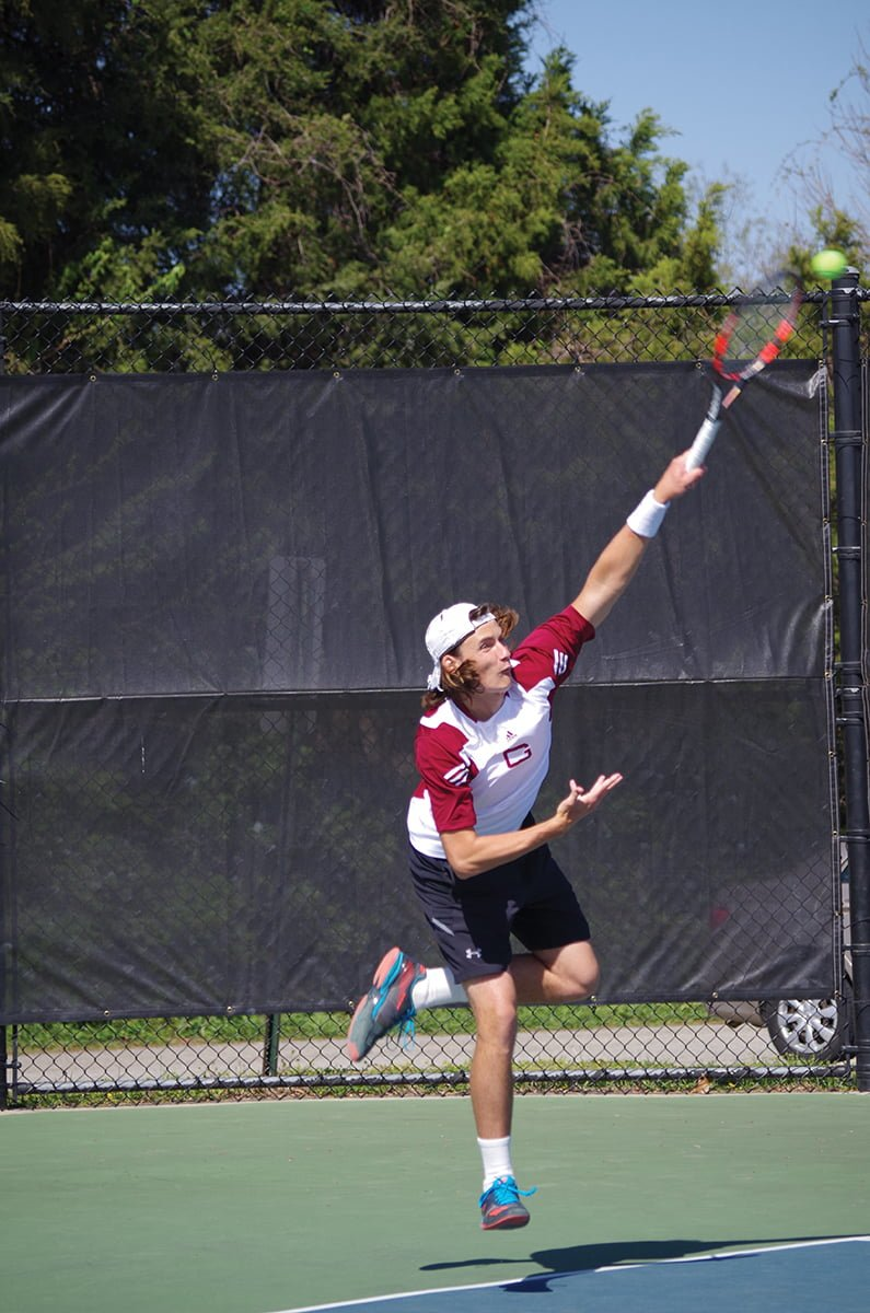 Sophomore Tate Godwin hits a serve in a doubles match against Roanoke College on Tuesday, April 17, 2018. // Photo by Andrew Walker/The Guilfordian