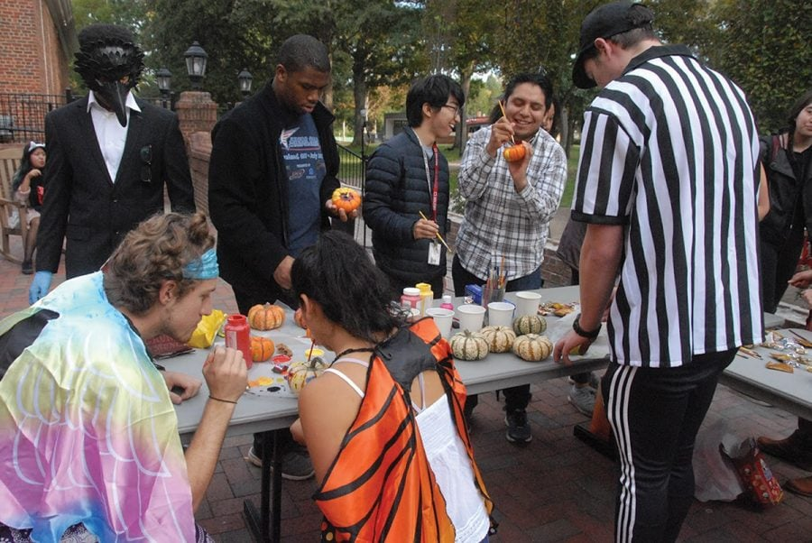 Students gather outside of Founders to paint pumpkins and celebrate Halloween. People came in costume and they were able to try different candy from different parts of the world. //Photo By Ezra Weiss/The Guilfordian