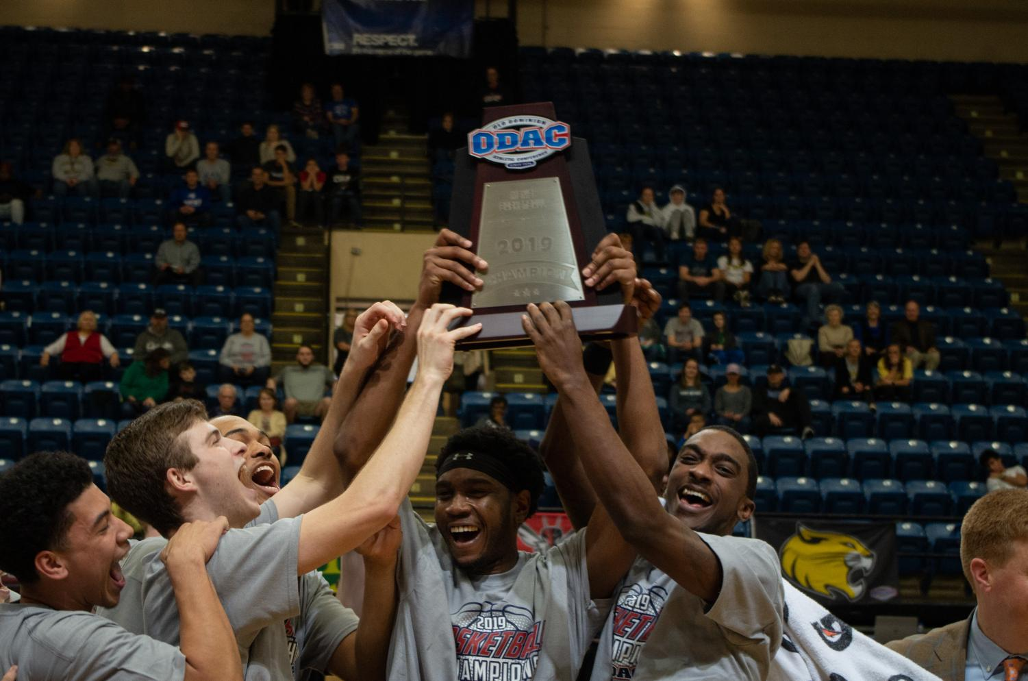 Senior forward Marcus Curry holds up the ODAC Tournament Championship trophy. Curry had 10 points in the victory.