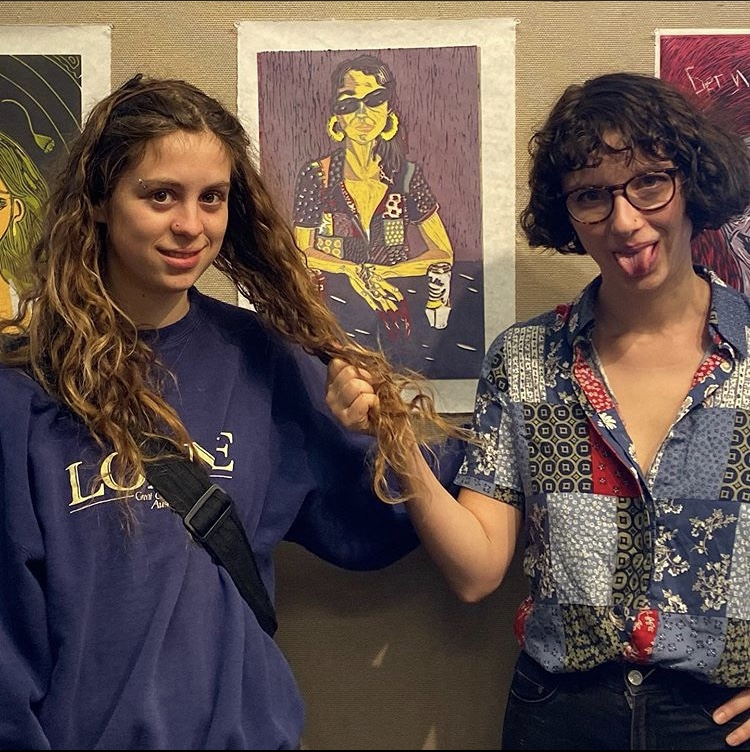 """Junior Tessa Young and senior Tay Bomstein pose in front of Bomstein's woodcut """"Mango Claw"""", which won the Best in Show prize."""