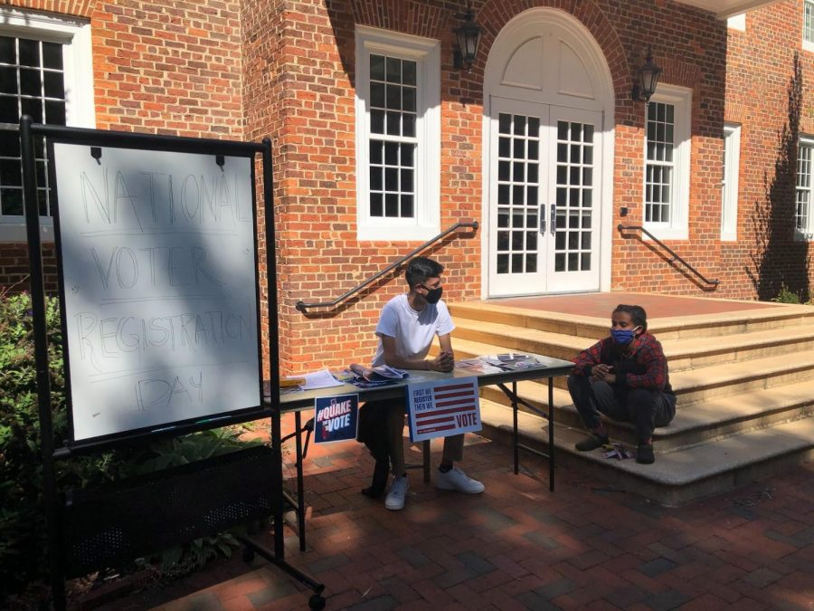 Kalkidan Miller and Isaac Collins wait tables outside Founders Hall to help students register to vote.