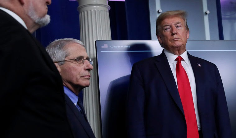 President Donald Trump looks over at National Institute of Allergy and Infectious Diseases Director Dr. Anthony Fauci as CDC Director Robert Redfield looks on the president returning to the daily coronavirus task force briefing at the White House in Washington, U.S., April 17, 2020
