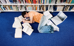 A student taking a nap to exercise self care and deal with the stress of school work.